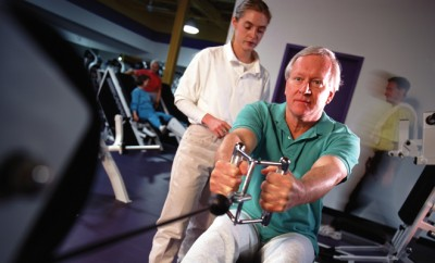 Senior man exercising under personal trainer in gym