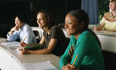 Group of college students in classroom, smiling, side view